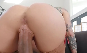 Tattooed pornstar wearing nylons fucks black dude on the couch
