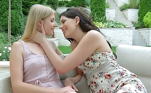 Two beautiful starlets giving a kiss and licking outdoors